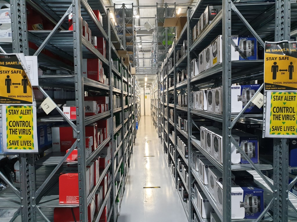 Unirack industrial shelving, fully stocked with auto parts products with a two-tier system in the background