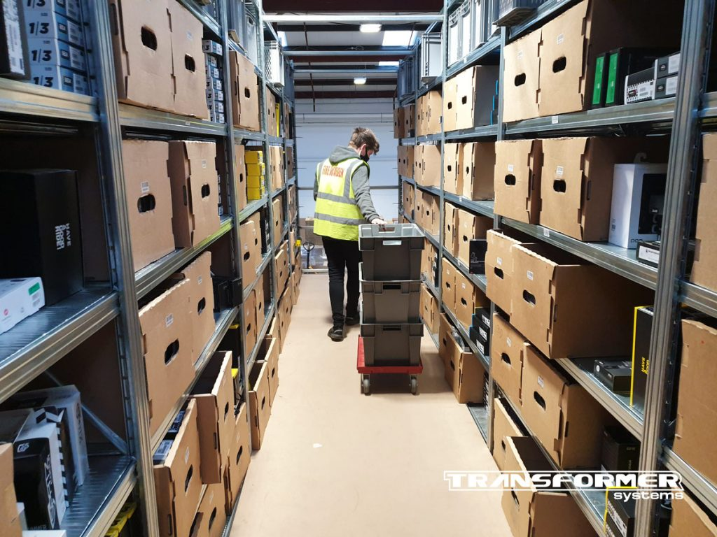 Two-Tier Shelving System with 12mm MDF Layered on Steel Walkways. Warehouse operative using picking boxes on floor dolleys whilst picking goods.