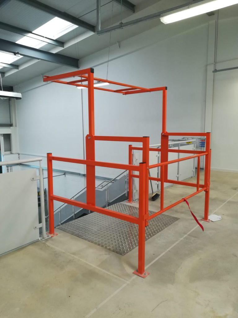 Epoxy powder coated orange, standard pallet gate with edge and wear protection for the mezzanine.