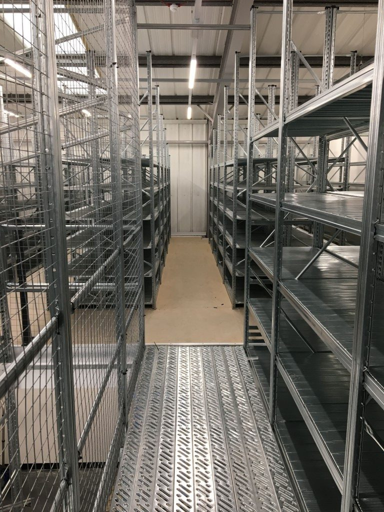 Two-tier shelving walkway, attached alongside a mezzanine floor.